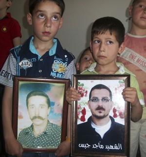 Crianças seguram retratos de seus pais, que teriam sido mortos por forças do governo sírio, durante visita de observadores da ONU a Kafr Takharim, subúrbio de Idlib, nesta segunda-feira (28) (Foto: Reuters)