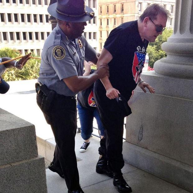 Policial Leroy Smith ajuda homem durante manifestação (Foto: Rob Godfrey via AP)