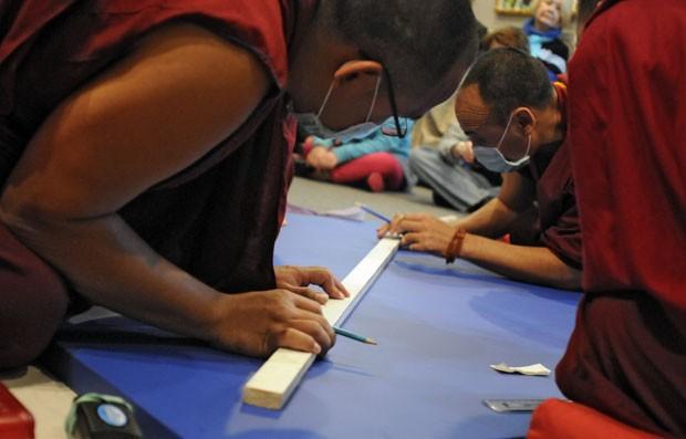 Monges traçam linhas da mandala que será preenchida com areia colorida (Foto: AP Photo/The Sun News, Charles Slate)