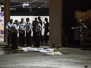 Polícia israelense ao lado de corpo de palestino após ataque a estação em Beersheba (Foto: Tsafrir Abayov/AP)