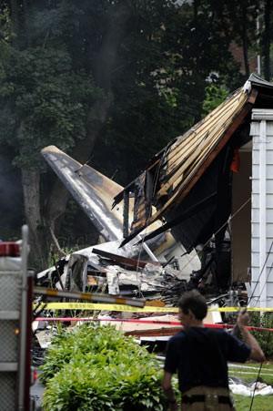 Bombeiro observa o local da queda do avião sobre casa em East Haven, Connecticut, nesta sexta-feira (9) (Foto: Fred Beckham/AP)