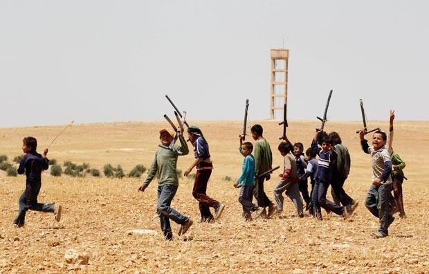 Crianças sírias cantam com armas de mentira durante treinamento 'militar' em área rural de Hama na quarta-feira (28). As fotos foram divulgadas nesta quinta (29) (Foto: Nour Fourat/Reuters)