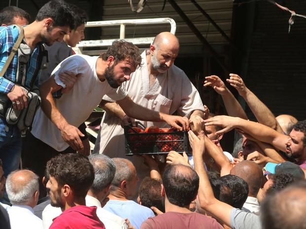 Sírios tentam comprar produtos frescos trazidos por rebeldes trazidos após a abertura de corredor humanitário, na quarta-feira (11), em Aleppo, no norte da Síria (Foto: Abdalrhman Ismail/ Reuters)