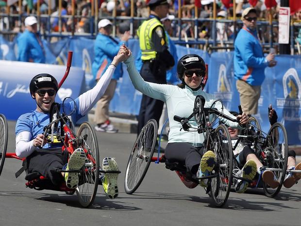 Patrick Downes e Jessica Kensky perderam uma perna cada no atentado da Maratona de Boston em 2013; neste ano, eles voltaram a participar da competição, mas agora sobre rodas (Foto: AP Photo/Elise Amendola)