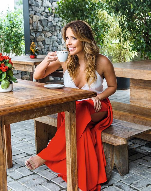 . (Foto: Renata toma um  café na área externa.  O espaço de convivência com bancos de madeira  é utilizado pelos frequentadores do restaurante Cafecito.)