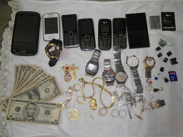 Celulares, relógios, joias e dólares foram encontrados na residência do suspeito (Foto: Divulgação/PM)