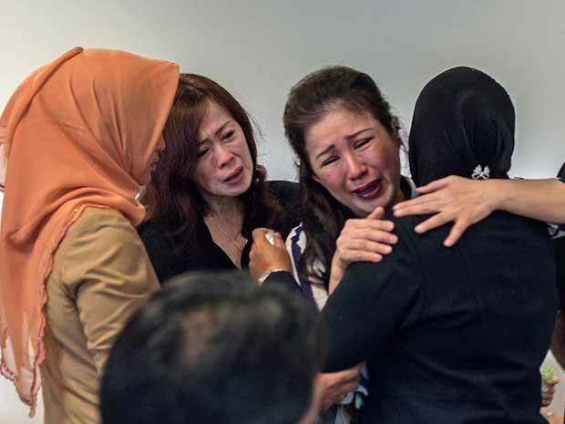 Familiares de passageiros do voo QZ-8501 se emocionam no Aeroporto de Surabaya, Java Oriental. (Foto: Juni Kriswanto / AFP Photo)