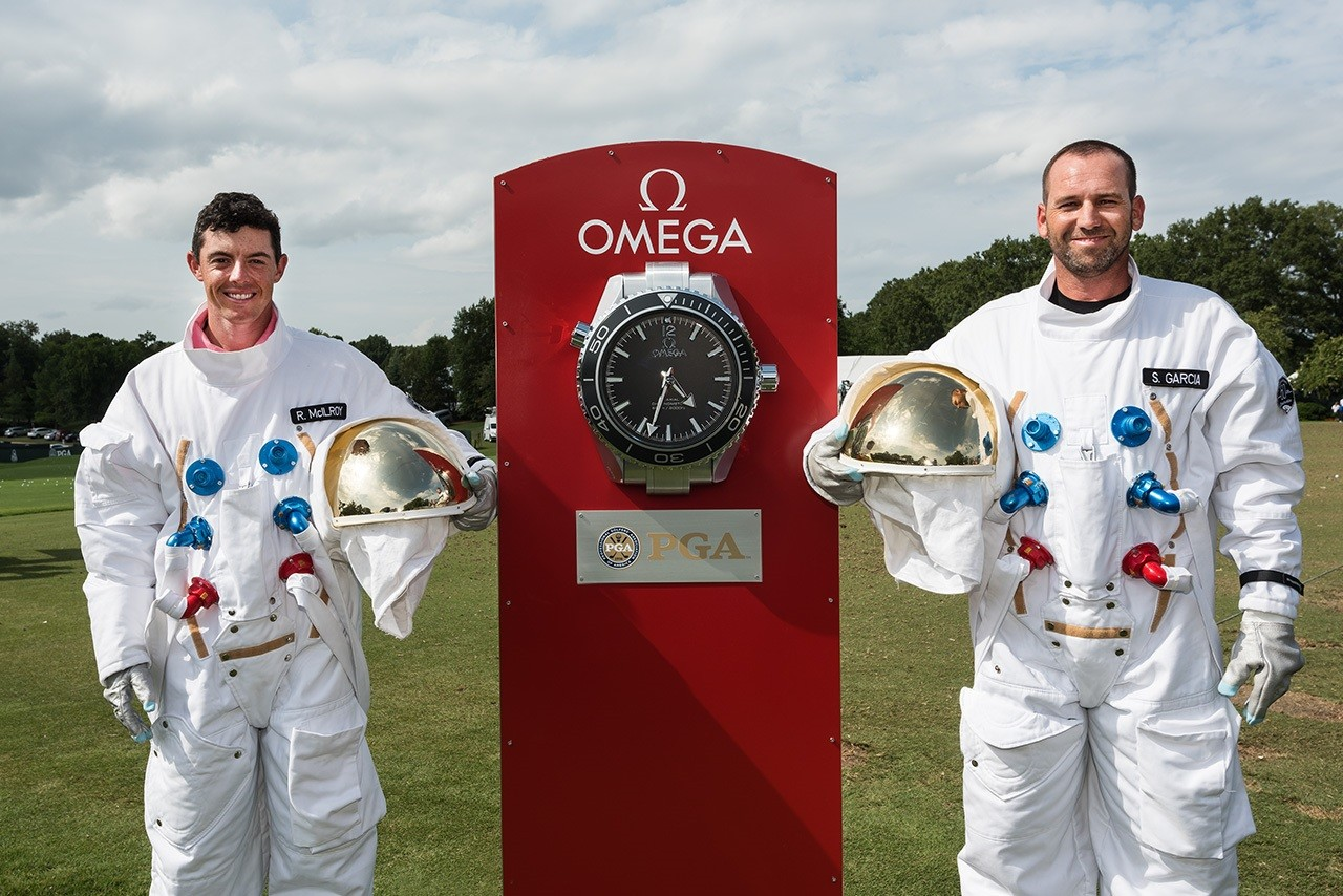 Os jogadores X e Y posam em frente a uma versão gigante do famoso Moonwatch (Foto: Divulgação)