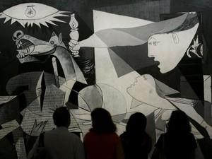 Visitantes observam em museu de Madri a famosa obra de Pablo Picasso que representou o bombardeio em Guernica (Foto: Bernat Armangue/AP)