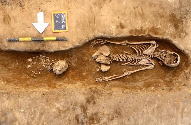 O esqueleto de uma mulher, enterrado com a cabeça pra baixo. O corpo de uma criança foi colocado entre suas pernas. (Foto: JOHN MOORE HERITAGE SERVICES)