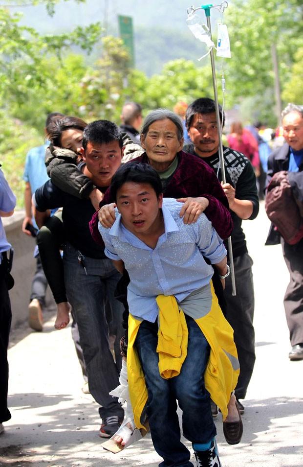 Chineses carregam feridos em terremoto (Foto: AFP)