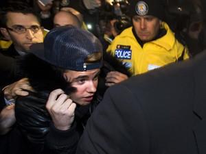 Justin Bieber é cercado por policiais e jornalistas ao se apresentar à polícia nesta quarta-feira (29). (Foto: Nathan Denette/The Canadian Press/AP)