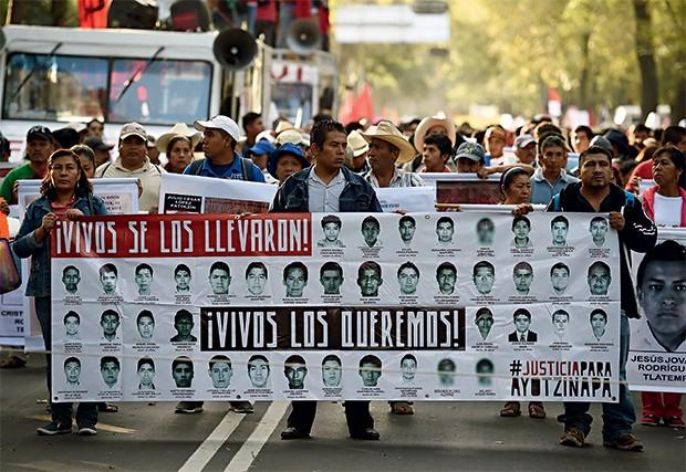 PROTESTOS Mexicanos carregam cartazes com os rostos dos 43 jovens mortos em Ayotzinapa. O terror do tráfico voltou (Foto: Ronaldo Schemidt/AFP)