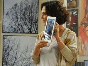 Manoela mostras as fotos que tirou de Fábio trabalhando (Foto: Guerra dos Sexos / TV Globo)