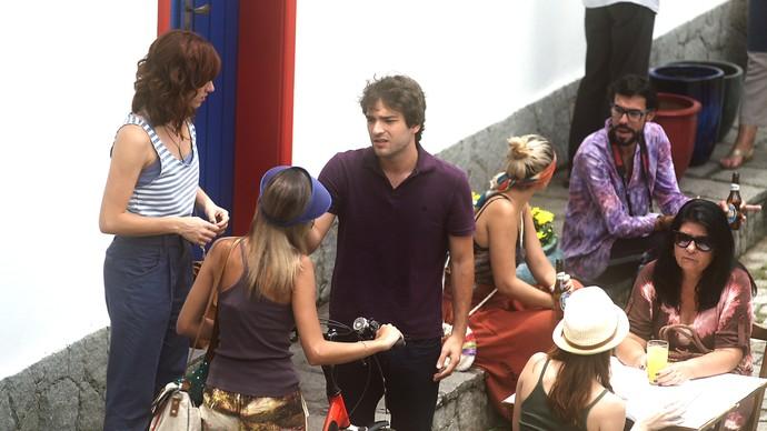 TIago tenta encontrar Isabela mostrando as fotos da estudante aos turistas (Foto: TV Globo)