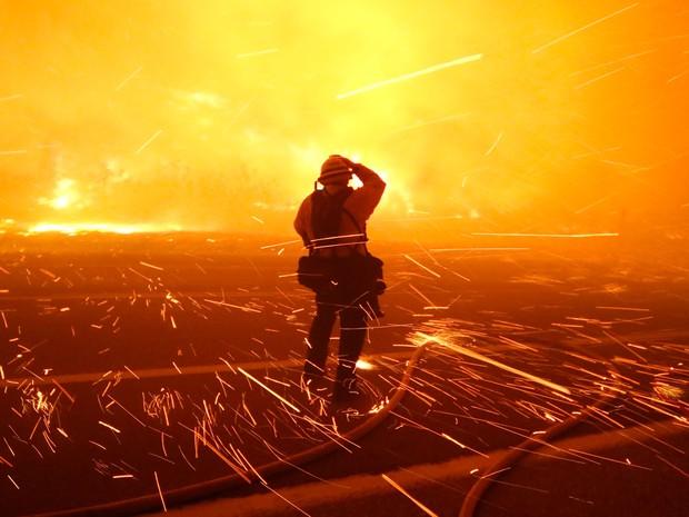 O fotógrafo Tod Sudmeier, especialista em incêndios, é atingido por faíscas durante incêndio no condado de Ventura, na Califórnia, no sábado (26) (Foto: Reuters/Gene Blevins )