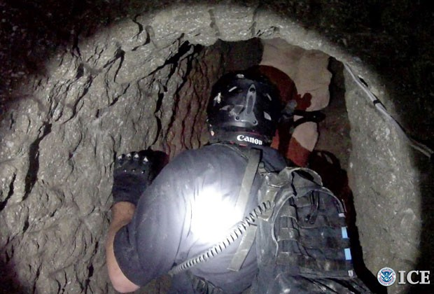 Agente de controle de fronteiras dos EUA entra em túnel usado para o tráfico de drogas do México para o país (Foto: Policía de Imigracão e Aduanas dos Estados Unidos/AP )