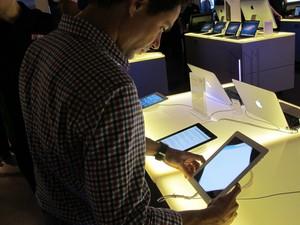 Usuário testa o iPad enquanto usuários compram o iPhone 5 (Foto: Amanda Demetrio/G1)