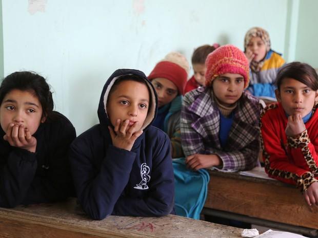 Crianças assistem aula de curdo; língua foi banida por Damasco, mas agora o governo local criou um currículo nas escolas primárias que estão sob administração curda (Foto: Delil Souleriman/ AFP)