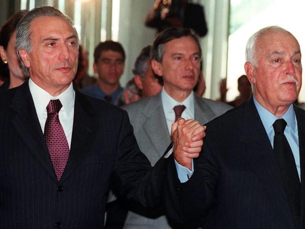 O então presidente da Câmara dos Deputados Michel Temer é visto de mãos dadas com Antônio Carlos Magalhães durante confraternização de natal no Congresso Nacional, em Brasília, em dezembro de 1998 (Foto: Dida Sampaio/Estadão Conteúdo/Arquivo)