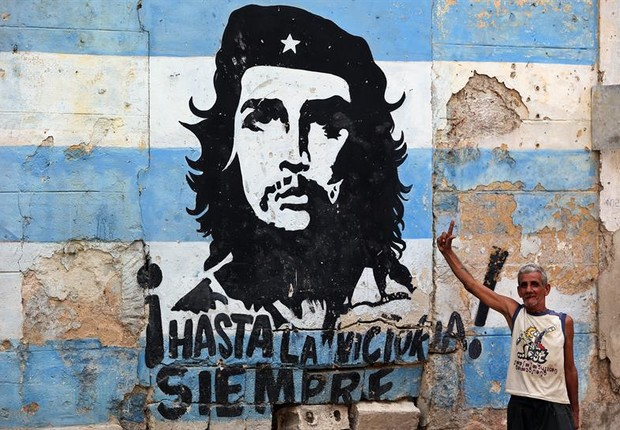 Cidadão cubano posa ao lado de grafite em homenagem ao líder revolucionário Che Guevara em Havana (Foto: Alejandro Ernesto/EFE)