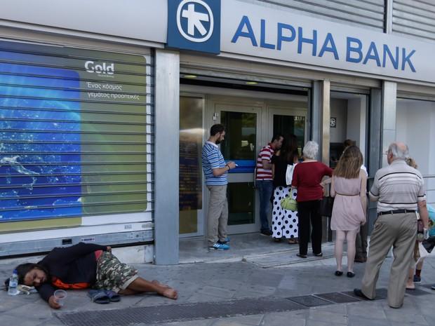 Pessoas fazem fila para usar um caixa eletrônico enquanto uma pessoa pede esmolas em Atenas, na Grécia. O país chegou a um acordo com seus credores, mas terá que fazer reformas trabalhistas e das aposentadorias, além de privatizações e aumento de impostos (Foto: Thanassis Stavrakis/AP)