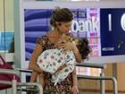 Grazi Massafera carrega filha no colo ao embarcar em aeroporto