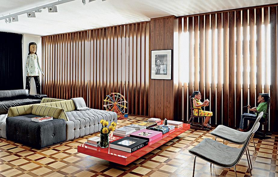 O design reto do mobiliário da casa de Paulo Borges, diretor da São Paulo Fashion Week, foi enriquecido por peças de artesanato, como o boneco de madeira Mulher, do sergipano Cícero Alves dos Santos e o Casal na Cadeira de Balanço, do alagoano Nilson