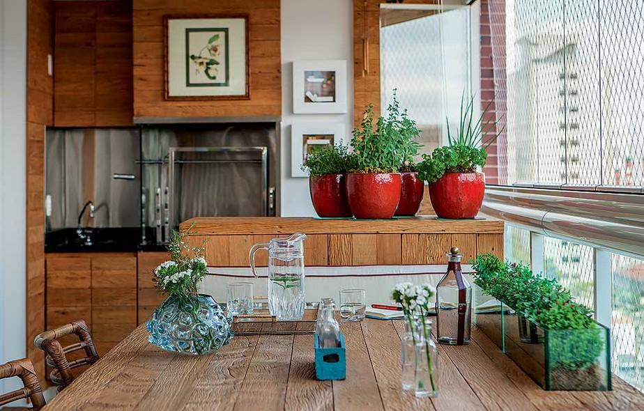 horta em vasos fica na varanda gourmet projetada pela designer de