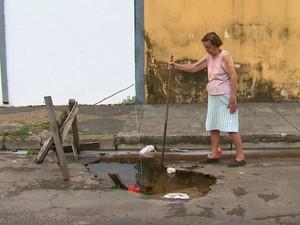 Moradores de São Carlos criam sinalização improvisada para os buracos (Foto: Felipe Lazzarotto/ EPTV)