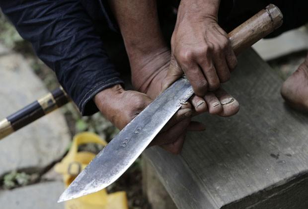 Chinês usa faca para cortar as unhas dos pés na aldeia de Basha, na província de Guizhou, na China (Foto: Jason Lee/Reuters)