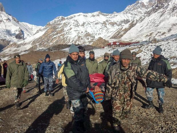 Vítima é resgatada de avalanche na região de Annapurna, no Nepal. Pelo menos 12 pessoas, incluindo oito alpinistas estrangeiros e um grupo de pastores tibetanos, foram mortos por nevascas fora de época e avalanches desencadeadas pelo ciclone Hudhud (Foto: Exército do Nepal/Reuters)