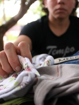 Mulher mostra roupa do filho, que serve para amenizar a saudade (Foto: Gustavo Arakaki/ G1 MS)