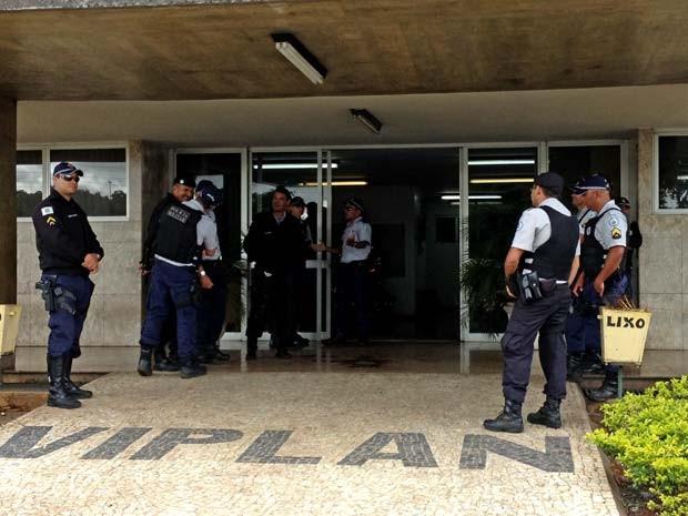 Policiais na entrada de uma das garagens do Grupo Viplan, que sofre intervenção do GDF nesta segunda-feira (23) (Foto: Lucas Salomão/G1)