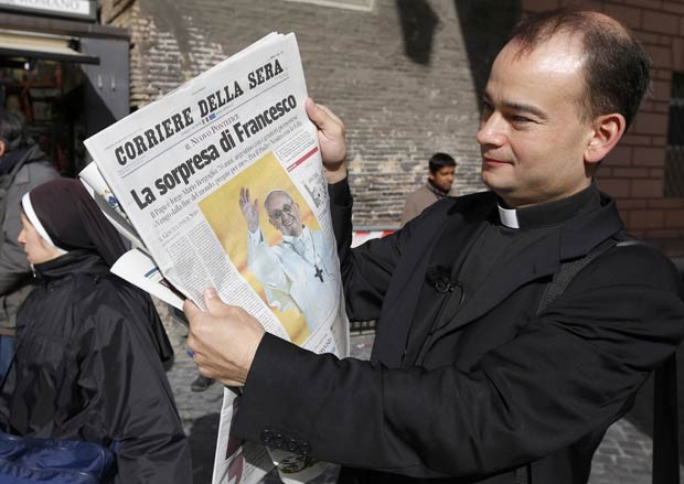 Padre observa edição de jornal com o título 'A surpresa de Francisco' nesta quinta-feira (14) no Vaticano (Foto: AFP)