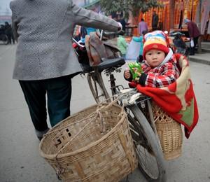 Bebê chinês em cesto de bicicleta (Foto: China Photos/Getty Images)