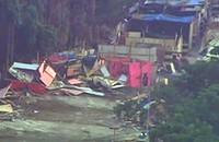 VÍDEO: veículo derruba barracos em terreno (Reprodução)