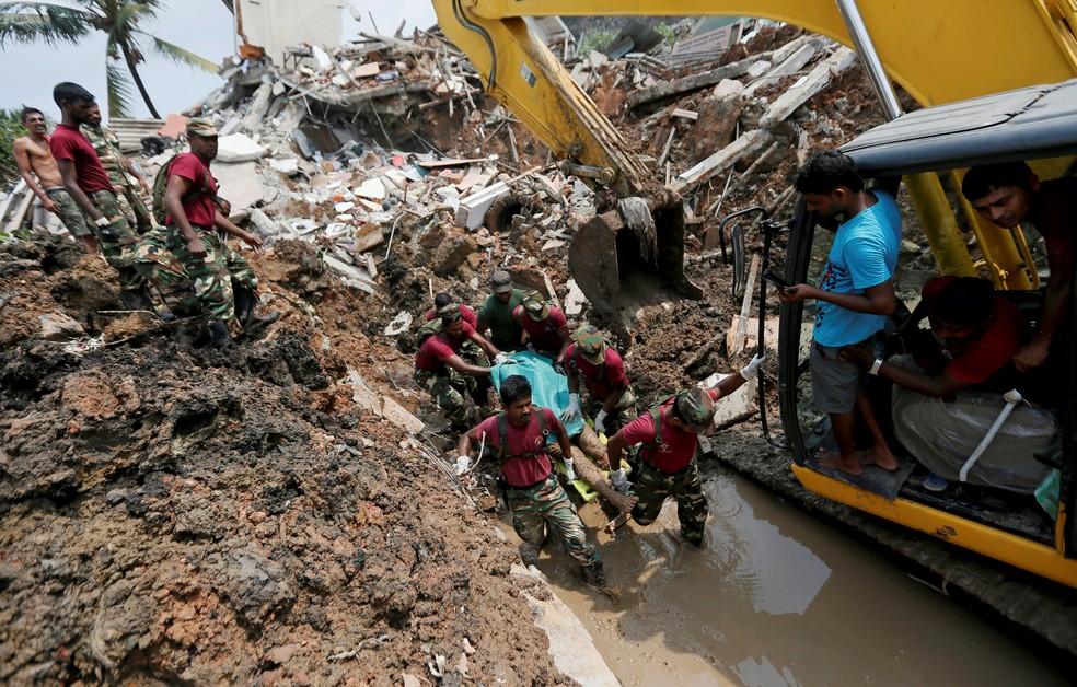 Membros do exército levam vítima morta durante missão de resgate depois que uma montanha de lixo desmoronou e enterrou dezenas de casas em Colombo, no Sri Lanka (Foto: REUTERS/Dinuka Liyanawatte)