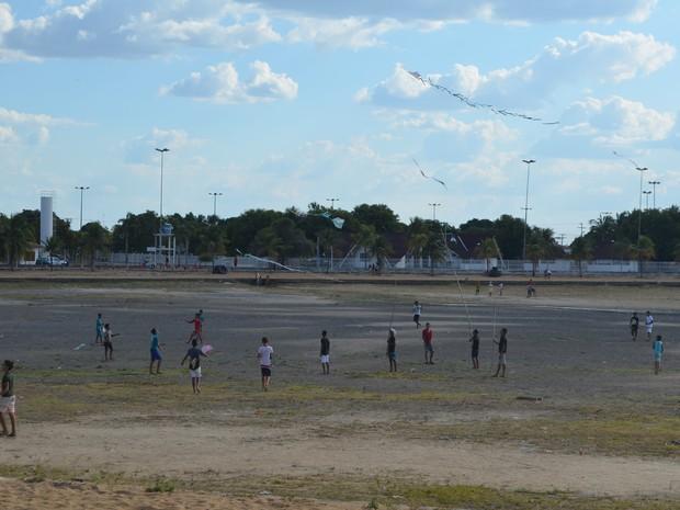 Crianças correm atrás de pipa dentro do lago (Foto: Marcelo Marques/ G1 RR)