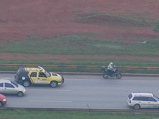 Policial militar pilota motocicleta sem capacete pelo acostamento da Esturutal, em Brasília, na manhã desta segunda-feira (14) (Foto: TV Globo/Reprodução)