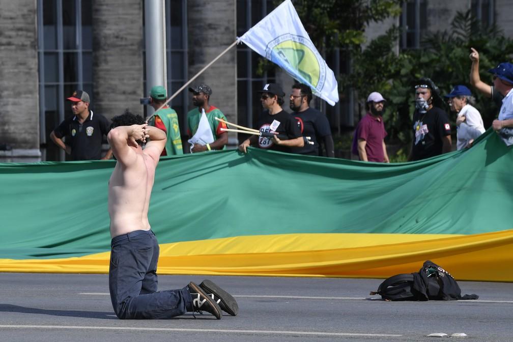 Um manifestante se ajoelha durante protesto contra Michel Temer, em Brasília (Foto: Mateus Bonomi/AFP)