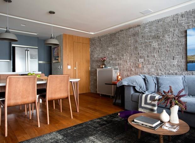 Com ambientes integrados, o living de 37 m², ganhou piso de peroba mica - à venda na Madeireira da Hora. A parede de apoio ao sofá foi revestida com Hardscape, da Ekko Revestimentos (Foto: Denílson Machado - MCA Estúdio/Divulgação )