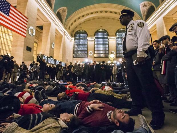 Policial observa ativistas no chão do terminal Grand Central, no centro de Nova York, nos EUA. O protesto na hora do rush pede justiça no caso de Eric Garner. Um júri decidiu livrar de acusações o policial branco que matou o homem negro por enforcamento (Foto: Adrees Latif/Reuters)