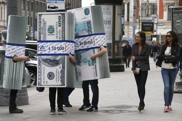 Mulheres riem ao encontrarem 'maços ambulantes de dinheiro' na rua durante campanha de marketing russa (Foto: Sergei Karpukhin/Reuters)