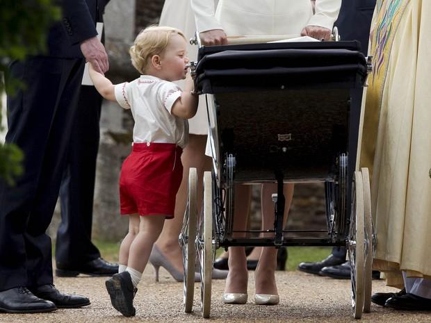 O príncipe britânico George observa no carrinho sua irmã, Charlotte, na chegada para o batizado dela na Igreja de Santa Maria Madalena em Sandringham, na Inglaterra (Foto: Matt Dunham/Reuters/Pool)