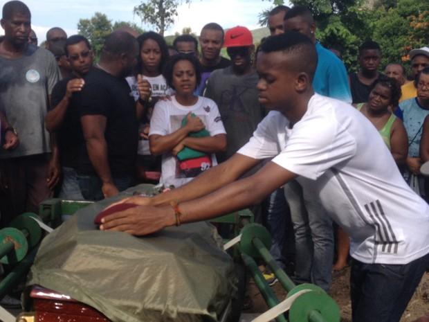 O filho do cabo deixa sobre o caixão uma boina do Exército (Foto: Matheus Rodrigues/G1)