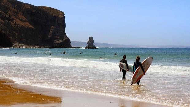 Dois surfistas prontos para entrar no mar na praia de Arrifana, Algarve Portugal (Foto: Carlos Caetano/shutterstock)