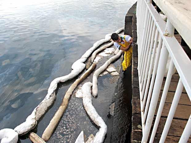 Funcionário trabalha em galeria; contenções são instaladas para impedir avanço de óleo sobre o Lago Paranoá (Foto: Lucas Nanini/G1)