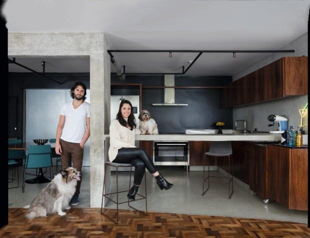 Cozinha Ana Paula e Gabriel posam no ambiente com bancada de cimento queimado, mesmo acabamento da parede à direita. No fundo, a superfície foi pintada com um tom grafite (Foto: André Klotz / Editora Globo)