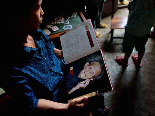 Neto de Luo Meizhen segura foto da mulher, que Segundo as autoridades chinesas tinha 127 anos ao morrer (Foto: Ed Jones/AFP)